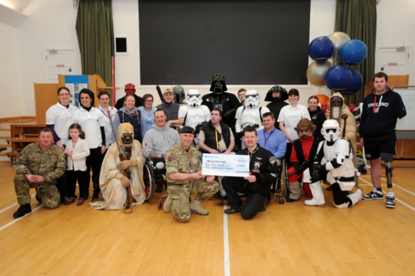 The UKG visit DMRC Headley Court and present a cheque to MediCinema